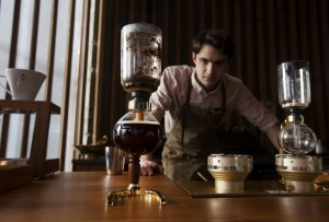 Barista Ryan McDonnell siphons coffee using vintage technology at the coffee experience bar of the Starbucks Reserve Roastery and Tasting Room. (David Ryder/Bloomberg)